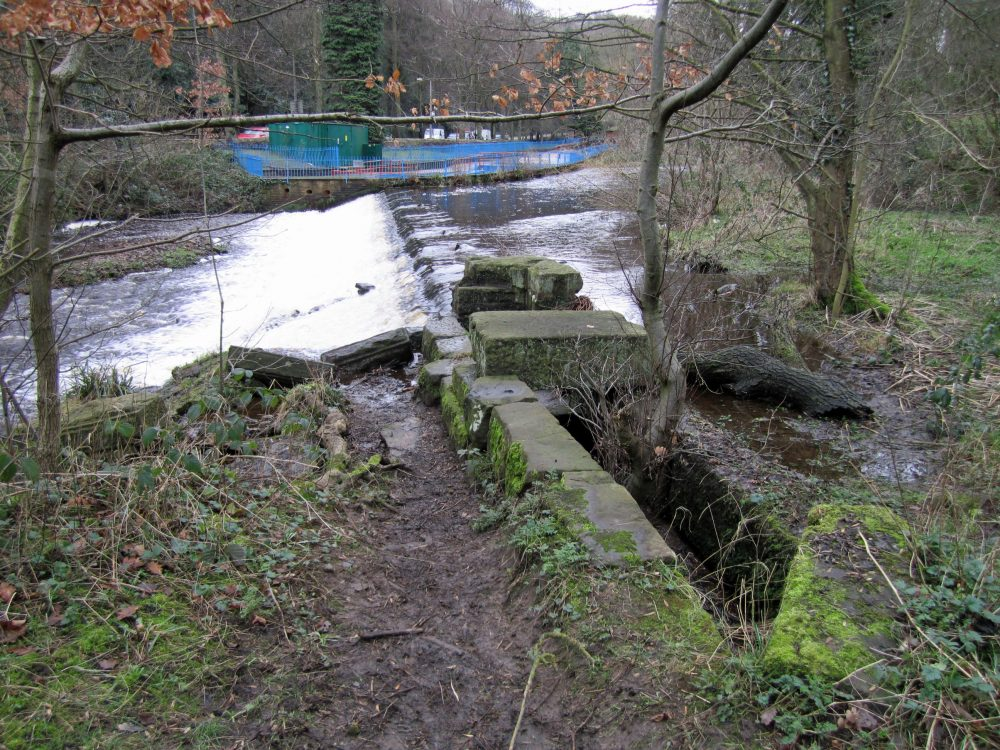 Large stone structure beside the Hollins Bridge Mill weir - probably the remains of the intake for the wheel pit. (RVCG, 2014)